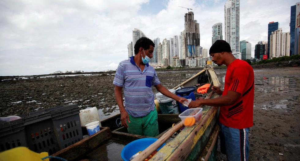 Pescadores trabajan frente al complejo de Punta Pacífica en el puerto pesquero de Boca La Caja, en Ciudad de Panamá, en medio de la pandemia de coronavirus. (EFE/ Bienvenido Velasco).
