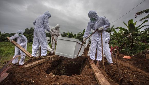 Trabajadores funerarios entierran a una víctima del coronavirus Covid-19 en un cementerio especial en Bogor, Indonesia. (Foto referencial, ADITYA AJI / AFP).