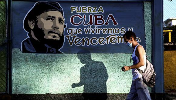 Un hombre camina junto a un mural que representa al fallecido líder cubano Fidel Castro en La Habana, Cuba, el 13 de agosto de 2021. (Foto de YAMIL LAGE / AFP).