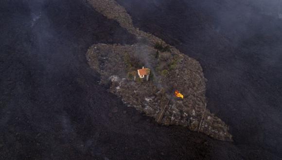 En esta foto proporcionada por iLoveTheWorld, una casa permanece intacta mientras la lava fluye después de que un volcán entró en erupción cerca de Las Manchas en la isla de La Palma en Canarias, España. (Alfonso Escalero / iLoveTheWorld vía AP).