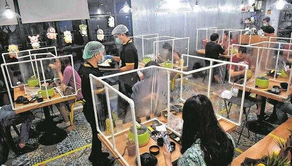 ¿Cómo será salir a comer? Penguin Eat Shabu hotpot, un restaurante en Bangkok, ha diseñado este sistema de separación de las personas por medio de plásticos ¿Podremos adaptarnos así en Perú? (Imagen: AFP)