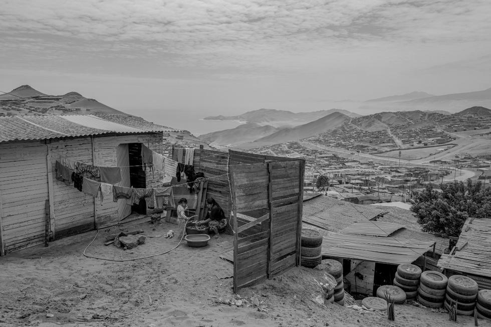 SOBREVIVIR EN EL DESIERTO. Kimberly Cruz y su niña lavan ropa en los exteriores de su vivienda, ubicada en el asentamiento humano PROFAM, en el distrito de Santa Rosa, al norte de Lima.  (Foto: Musuk Nolte)