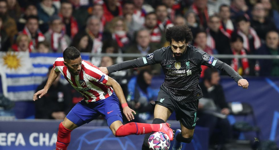 Atletico Madrid's Renan Lodi, left, and Liverpool's Mohamed Salah fight for the ball during a 1st leg, round of 16, of the Champions League soccer match between Atletico Madrid and Liverpool at the Wanda Metropolitano stadium in Madrid, Tuesday, Feb. 18, 2020. (AP Photo/Manu Fernandez)