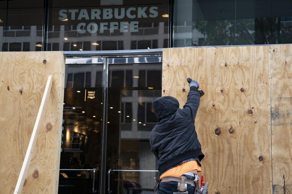 Las tablas de madera protegen un local de Starbucks cerca de la Casa Blanca en Washington (Estados Unidos). Las empresas se blindan ante el temor de manifestaciones por las elecciones. (Álex Edelman / AFP).