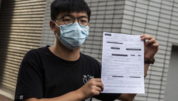El activista prodemocracia Joshua Wong habla con los medios de comunicación mientras sostiene un documento de fianza después de salir de la estación central de policía en Hong Kong. (ISAAC LAWRENCE / AFP)