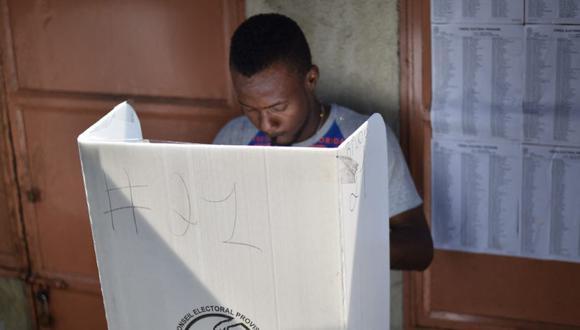 Un hombre emite su voto en el mercado Canape Vert, en la capital haitiana de Puerto Príncipe, el 29 de enero de 2017 durante las elecciones locales y legislativas. (Foto: HECTOR RETAMAL / AFP).