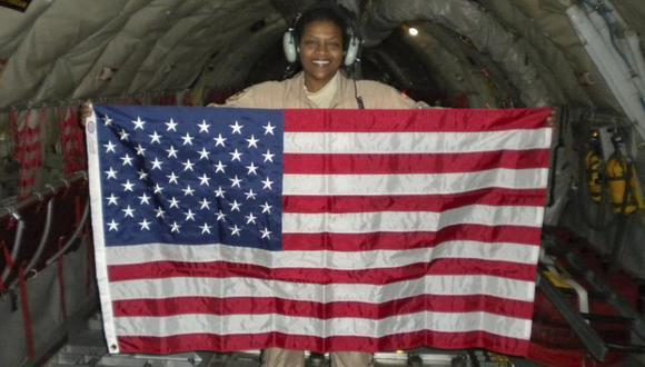 Foto del 28 de diciembre del 2009 en la que se ve a la teniente coronel retirada de la Fuerza Aérea Stephanie Davis sosteniendo una bandera de EE.UU. durante un vuelo por Pakistán y Afganistán. (Cortesía de Stephanie Davis vía AP)