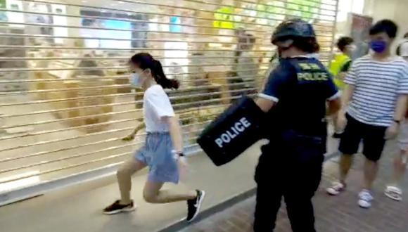 Una niña de 12 años corre mientras es intervenida por la policía de Hong Kong. (Reuters).