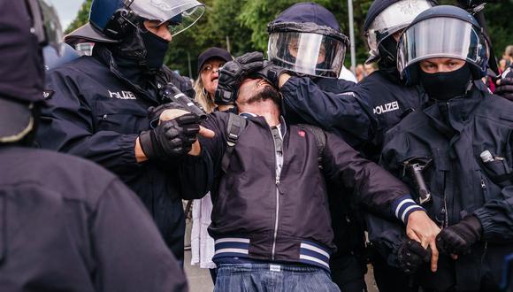 La policía detiene a un manifestante en Berlín, Alemania, el 1 de agosto de 2021, durante una protesta contra las medidas adoptadas por la pandemia de coronavirus. (EFE / EPA / CLEMENS BILAN).