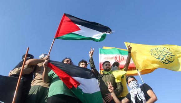 Los partidarios de Hezbolá en Líbano levantan banderas de Palestina e Irán, durante una protesta contra Israel en el área sur de Khiam, en la frontera con Israel, frente a la ciudad de Metula, en el norte de Israel, el 14 de mayo de 2021. (Foto: Mahmoud Zayyat/ AFP)