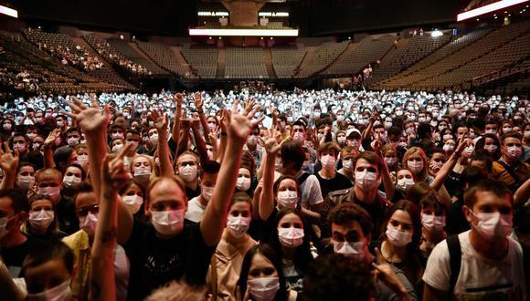 La gente levanta la mano antes del inicio de un concierto de prueba de la banda de rock francesa Indochine y el DJ francés Etienne de Crecy, cuyo objetivo es investigar cómo estos eventos pueden tener lugar de manera segura en medio de la pandemia de coronavirus Covid-19. (Foto de STEPHANE DE SAKUTIN / AFP).