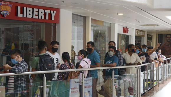 Empleados de un centro comercial y público en general hacen cola para vacunarse contra el coronavirus Covid-19 en la India (Foto de Diptendu DUTTA / AFP).