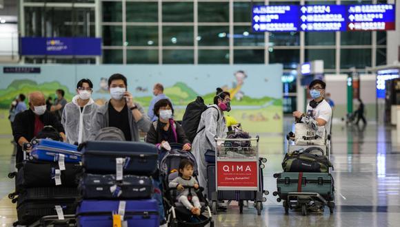 Pasajeros usan equipos de protección y mascarillas como medida de precaución contra el coronavirus en la sala de llegadas del aeropuerto internacional de Hong Kong, el 24 de marzo de 2020. (Foto referencial, ANTHONY WALLACE / AFP).
