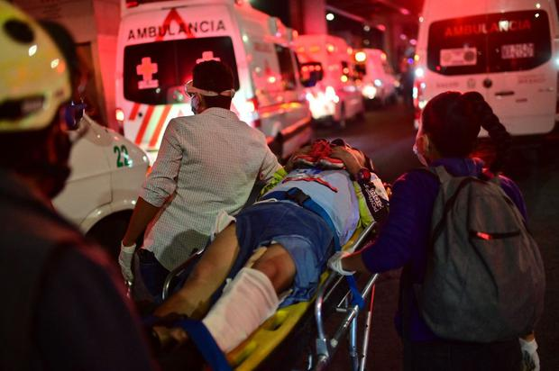 Emergency workers carry an injured person on a stretcher after a one-meter overpass partially collapsed in Mexico City.  (Photo by Pedro PARDO / AFP).