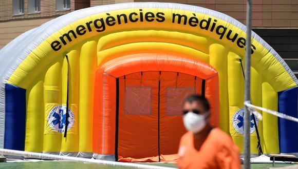 Un hombre con una máscara facial pasa frente a un hospital de campaña establecido para casos de coronavirus en las afueras del Hospital Universitario Arnau de Vilanova, en Lleida, Cataluña, España. (Foto por Pau BARRENA / AFP).
