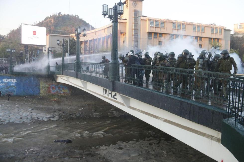 Miembros de carabineros observan a un manifestante que se encuentra inconsciente en el río Mapocho tras ser empujado por un agente que reprimía una protesta contra el presidente Sebastián Piñera. (EFE/ Sebastián Silva).