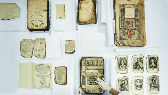 Algunos de los documentos recuperados tras el incendio de 1943 son cuidadosamente reubicados por los restauradores para su exhibición pública. (Foto: Fidel Carrillo)