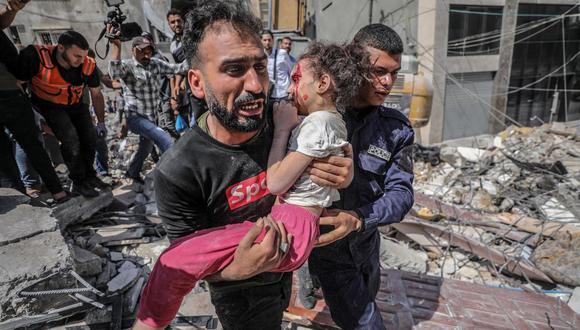 Un palestino evacua a su hija herida de entre los escombros de una casa destruida después de un ataque aéreo de Israel en la ciudad de Gaza, el 16 de mayo de 2021. (EFE / EPA / HAITHAM IMAD).
