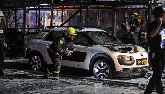 Los bomberos israelíes revisan los vehículos dañados en la ciudad israelí de Holon, cerca de Tel Aviv. (Foto de Ahmad GHARABLI / AFP).