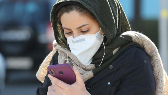 El carácter desconocido del coronavirus COVID-19 sirve de terreno fértil para alimentar las 'fake news'. En esta foto de inicios de marzo, una mujer revisa su celular en Teherán. (Photo by ATTA KENARE / AFP)