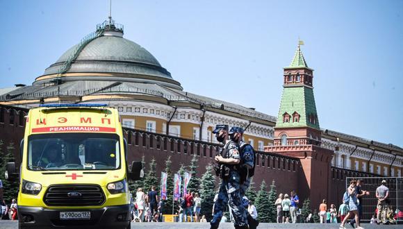Los militares de la Guardia Nacional de Rusia caminan por la Plaza Roja frente a una ambulancia en el centro de Moscú el 18 de junio de 2021, en medio de la crisis relacionada con la pandemia de coronavirus. (Foto de Alexander NEMENOV / AFP).