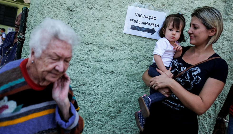 """A sign reading """"Yellow Fever Vaccination"""" is seen next to citizens that are waiting to receive the yellow fever vaccine in Sao Paulo, Brazil October 25, 2017. REUTERS/Nacho Doce"""