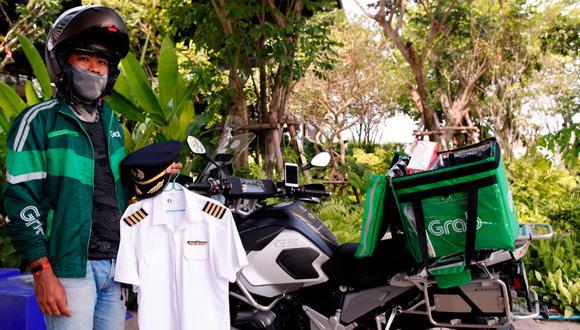 Todas las mañanas, Thanun Khantatatbumroong se pone la chaqueta verde con el logotipo de Grab, la compañía de reparto a domicilio, y sale a las calles de Bangkok con su BMW, que contrasta con las motos de menor cilindrada de otros repartidores. Foto:  EFE/EPA/RUNGROJ YONGRIT