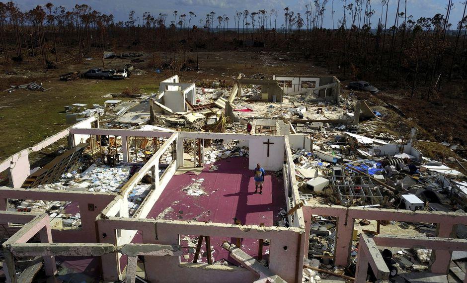 El pastor Jeremiah Saunders posa para una foto entre las ruinas de su iglesia que fue destruida por el huracán Dorian en High Rock, Gran Bahama, Bahamas. (Foto AP / Ramon Espinosa).