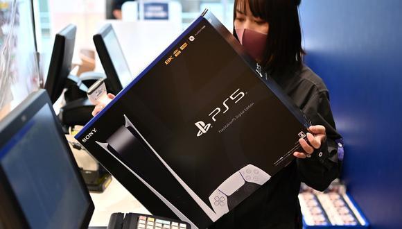 Un empleado prepara la nueva consola de juegos Sony PlayStation 5 para un cliente el primer día de su lanzamiento, en una tienda en Kawasaki, prefectura de Kanagawa (Japón), el 12 de noviembre de 2020. (AFP / CHARLY TRIBALLEAU).