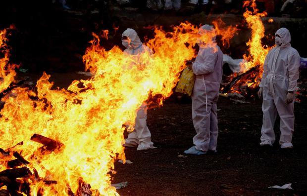 Family members walk between funerals burning personal protective equipment while performing funeral rites for victims of India's Gopal-19 corona virus.  (EFE / EPA / Sanjeev Gupta).