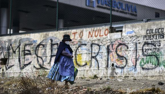 Una mujer pasa junto a un graffiti contra el candidato presidencial Carlos Mesa, en El Alto, Bolivia, el 17 de octubre de 2020. (Foto de Ronaldo SCHEMIDT / AFP).