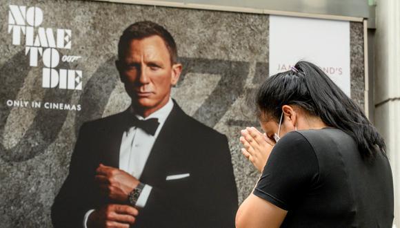"""Una mujer reza en el Santuario de Erawan frente a un cartel publicitario que presenta a Daniel Craig en la nueva película de James Bond """"No Time to Die"""" en Bangkok el 28 de septiembre de 2020. Mladen ANTONOV / AFP"""