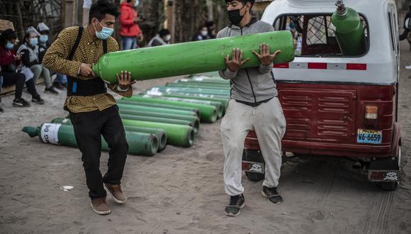 Dos hombres cargan un balón de oxígeno en Villa El Salvador, en abril. (Foto: ERNESTO BENAVIDES / AFP)