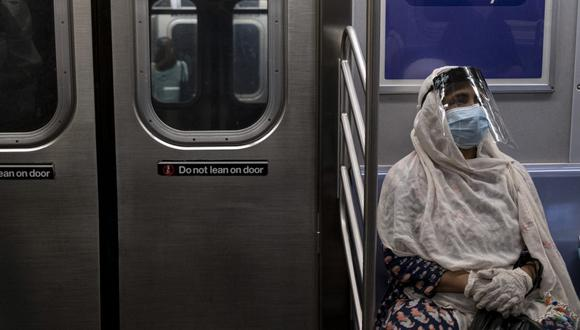 (FILES) In this file photo taken on July 16, 2020 (FILES) In this file photo taken on July 16, 2020, a woman wearing a face mask and shield sits in a subway train during rush hour amid the coronavirus pandemic in New York City. - Public transport was already expected to show its best light in the United States to try to compete with the automobile, but the pandemic has reduced these efforts to nothing, and the sector fears that it will have to lay off again and reduce its supply. Tuesday morning rush hour in the Washington subway. Only four people are seated in the train. Since the pandemic broke in March, traveling standing up is just an old memory. (Photo by Johannes EISELE / AFP)