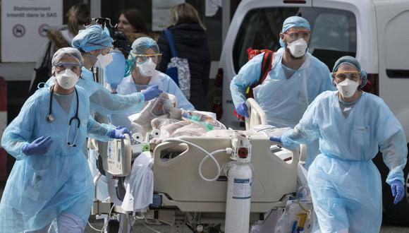 El personal médico lleva a un paciente de coronavirus hacia un helicóptero en el Hospital Emile Muller en Mulhouse, este de Francia. (Foto de SEBASTIEN BOZON / AFP).