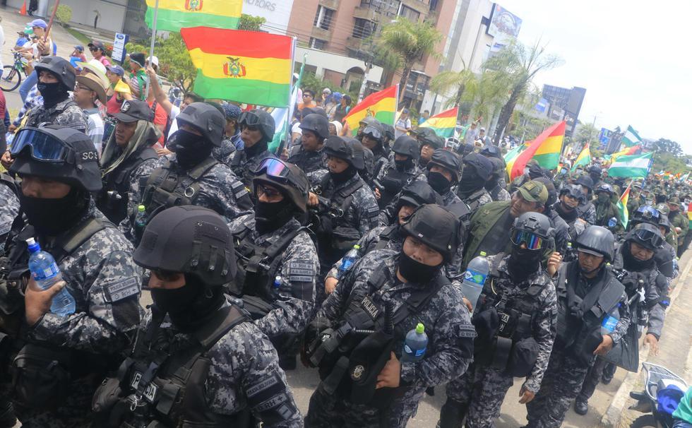 Un grupo de policías ondea la bandera tricolor de Bolivia mientras marcha en Santa Cruz junto a la población que exigen la renuncia de Evo Morales. (EFE/Juan Carlos Torrejón).