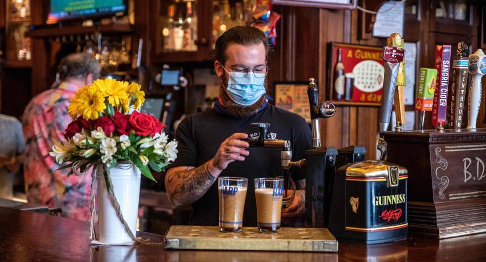 En esta foto de archivo tomada el 22 de mayo de 2020, un barman sirve bebidas a los clientes en un bar en Austin, Texas. (AFP / Sergio Flores).