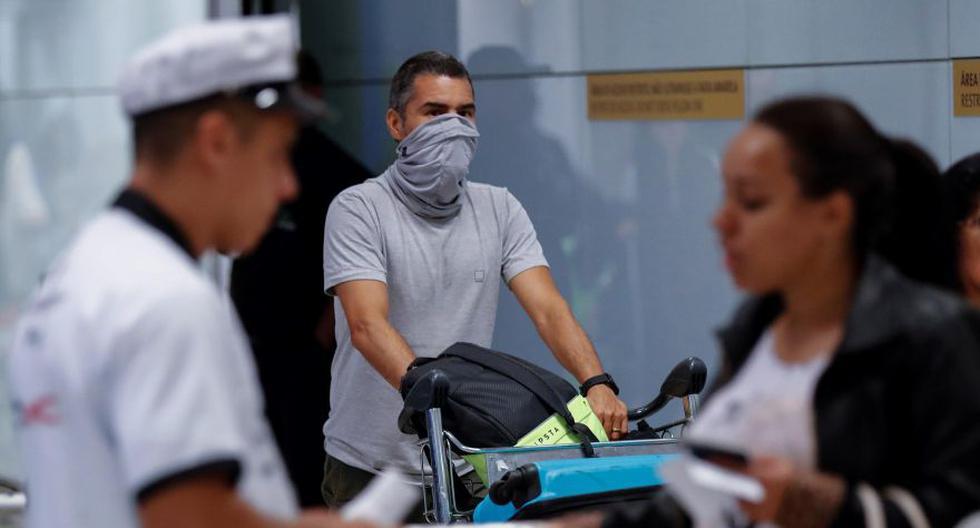 Pasajeros usan máscaras como precaución contra la propagación del nuevo coronavirus COVID-19 durante su llegada, el jueves, al Aeropuerto Internacional de Sao Paulo (Brasil). (Foto: EFE)