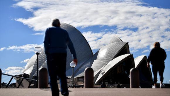 Esta imagen tomada el 26 de junio de 2021 muestra a personas caminando frente a la Ópera de Sídney durante el cierre por coronavirus en esa ciudad de Australia. (Foto de Saeed KHAN / AFP).