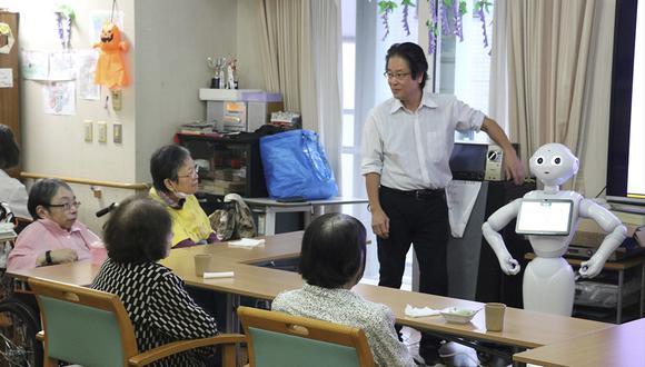 Varios ancianos participan en diferentes actividades de ocio protagonizadas por robots. (EFE)