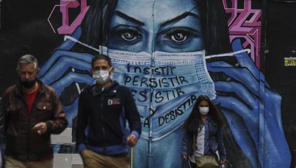 La gente usa mascarillas cerca de un mural en Bogotá el 14 de abril de 2021, en medio de la pandemia de coronavirus COVID-19. (Foto de Juan BARRETO / AFP).