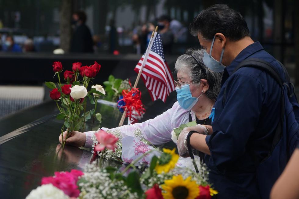 Las personas en Nueva York colocan flores en los nombres de las víctimas al borde de la piscina sur durante las ceremonias del 19° aniversario de los ataques del 11 de septiembre de 2001. (REUTERS/Carlo Allegri).
