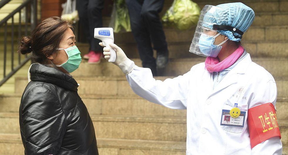 Una voluntaria (d), de la comunidad de Xuetianwan mide la temperatura corporal de una residente en la entrada de un mercado de vegetales, en el distrito de Yuzhong, municipalidad de Chongqing, en el suroeste de China, el 22 de febrero de 2020. Trabajadores y voluntarios del distrito de Yuzhong han cumplido con su deber en la batalla contra el brote por el nuevo coronavirus. (Xinhua/Wang Quanchao)
