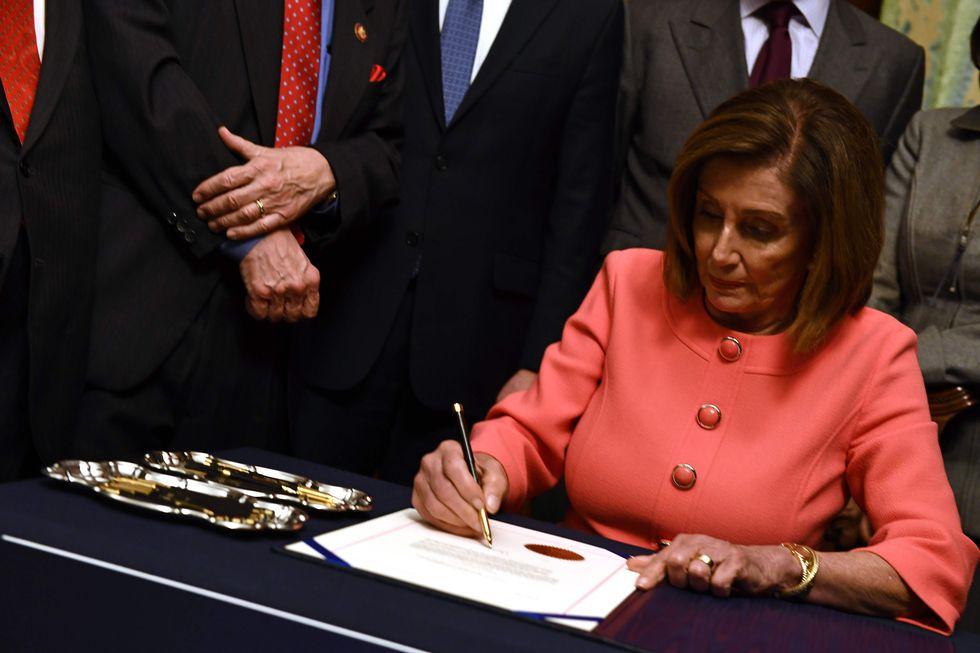 La presidenta demócrata de la Cámara de Representantes, Nancy Pelosi, firmó este miércoles los dos cargos de acusación contra Donald Trump, poco antes de que fueran transmitidos al Senado. (Foto: AFP)