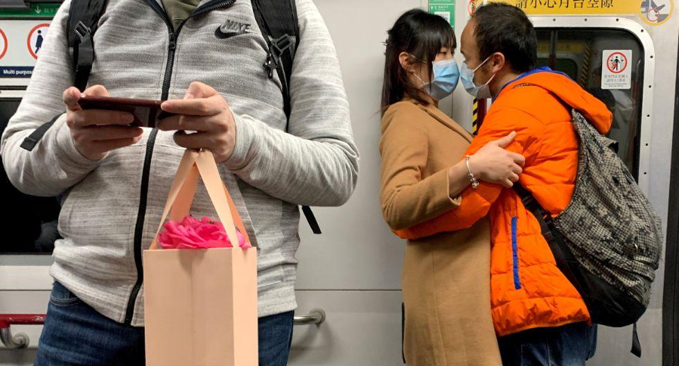 Una pareja con máscaras se abraza en un tren MTR, luego del estallido del nuevo coronavirus en el Día de San Valentín en Hong Kong. (Foto: Reuters)