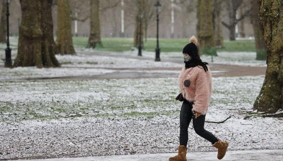 Imagen referencial. Una mujer camina en un parque en la nieve en el centro de Londres, Reino Unido, el 8 de febrero de 2021. (Foto: Tolga Akmen / AFP).