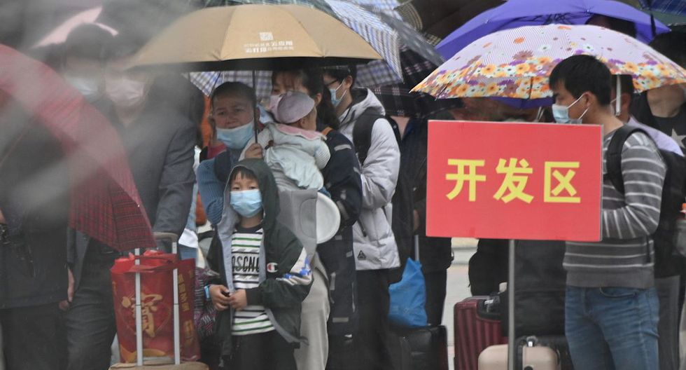 Las personas que llevan máscaras faciales hacen cola afuera para comprar boletos en la estación de trenes de Macheng, en la provincia central china de Hubei. (AFP)