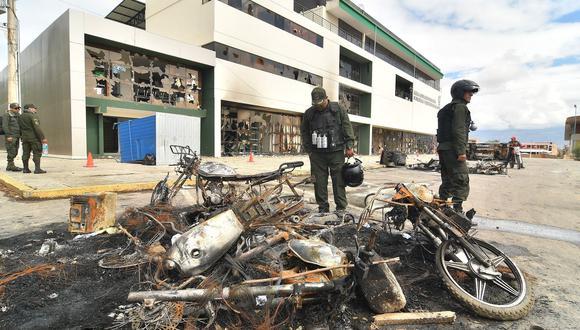 Policías bolivianos observan los destrozos provocados por grupos enardecidos que incendiaron una estación policial en Cochabamba. (EFE/Jorge Abrego).