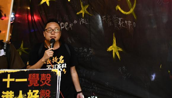 En esta foto de archivo, tomada en octubre de 2017, el activista Tam Tak-chi camina con una pancarta negra hacia la oficina de Enlace de China, después de una marcha de protesta anual en el día nacional de China, en Hong Kong. (Anthony WALLACE / AFP)