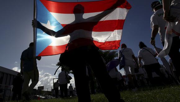 Imagen referencial en donde un hombre sostiene la bandera de Puerto Rico. REUTERS